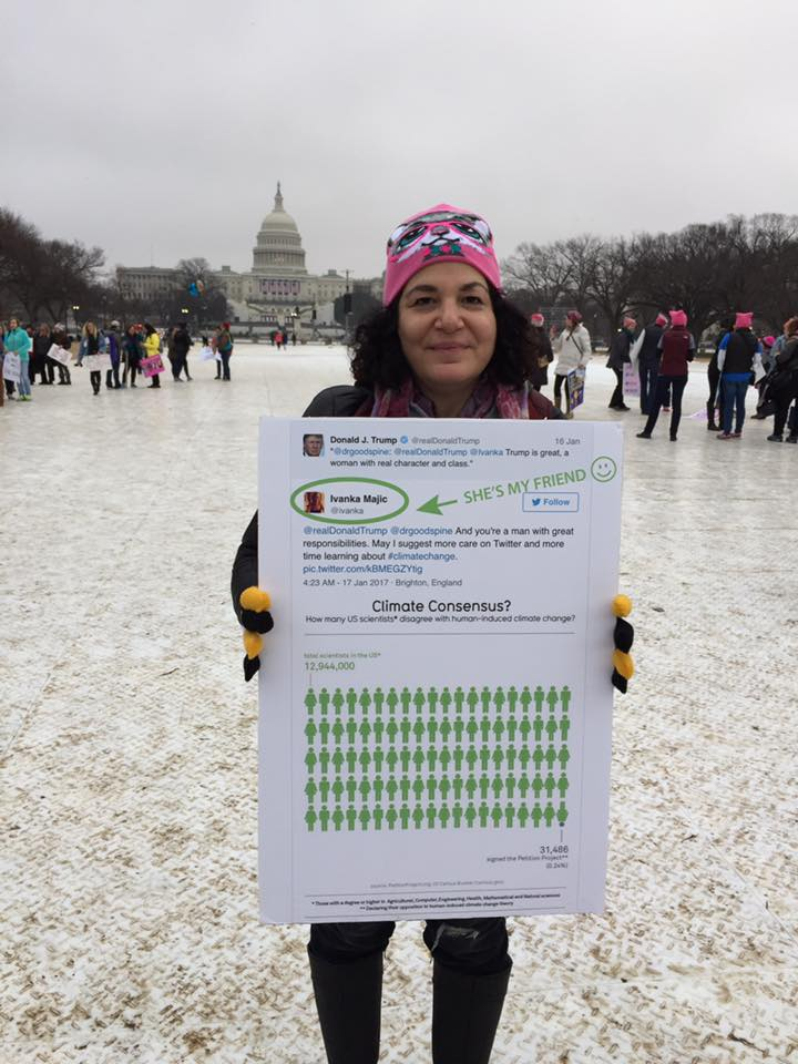 Beth Bell, founder of Green Product Placement holding a poster up with ivanka's climate change tweet at the women's march in Washington DC January 2017